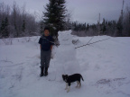 "Tyler Meekis and his pupppy ""Lady"" posing for a picture with his snow scuplur."