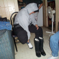 Here's Darlene getting ready to go to Sandy Lake. she's putting on thermal socks and winter boots. On the right peeking through