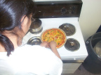 Crysal Rae prepares the pizza.