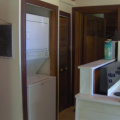 The hallway with the washer and dryer with the doorway to the entrance that leads to the other two bedrooms