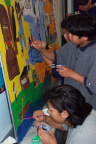 Bottom Left: Ruth Wassaykeesic (grade 9) takes a moment to help the grade 6/7 students with their mural.