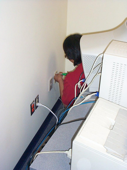 Darlene Rae installing a wall plate with network connector.
